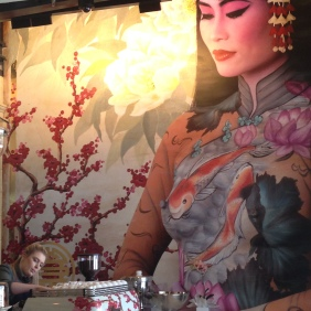 The beautiful wall painting by Emma Hack - Madame Hanoi - body painted and photographed, placed on a painted background