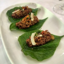 Betel leaves topped with sticky caramelised por