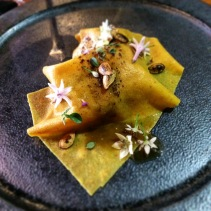 Pumpkin roasted with chilli, thyme and garlic covered with a pumpkin pasta sheet, praline, ash, toasted seeds, garlic puree and allium flowers