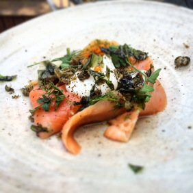 Manuka smoked ora king salmon, a poached egg, salmon pearls, soft herbs, served with wattle seed blini