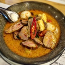 Red duck curry of roasted duck breast with cherry tomatoes, lychees and Thai basil