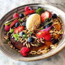 Ricotta Hotcake with seasonal berries, spiced syrup, nuts and seeds and vanilla triple cream