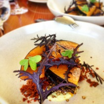 Pumpkin poached in aged beef fat with romesco powder, puffed buckwheat and mustard leaf