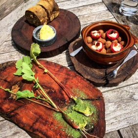 Gather bread with house churned butter and herb salt, radishes with butter and parsley powder, quandongs