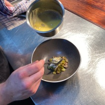 Plating up the Coorong mullet dish with leek, mushroom and chicken skin